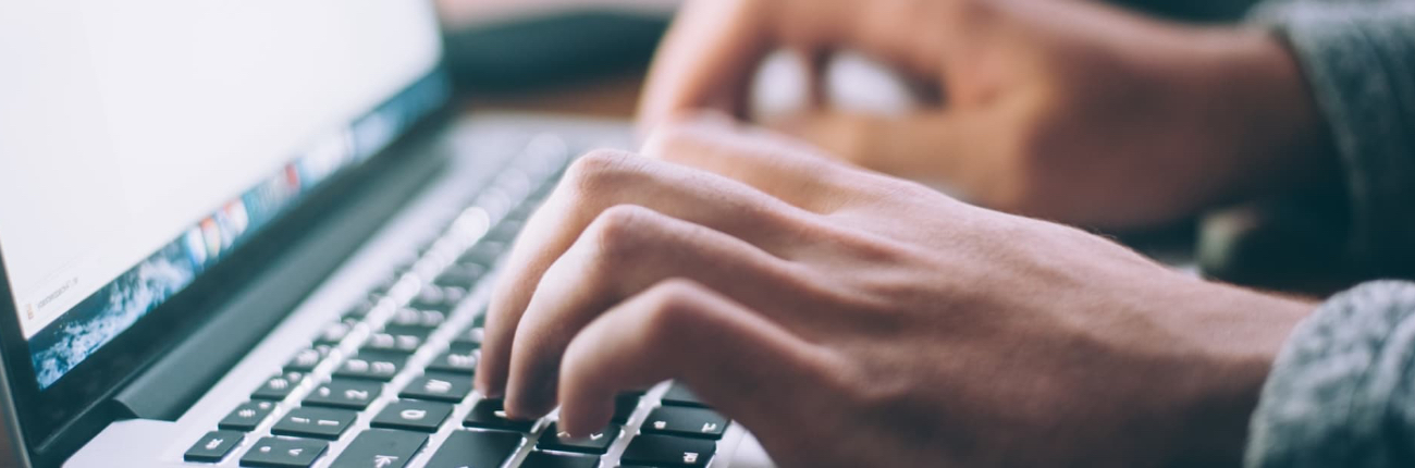 Photo of hands writing on a laptop.